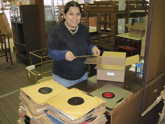 Alethea Perez packing phonograph records in store.