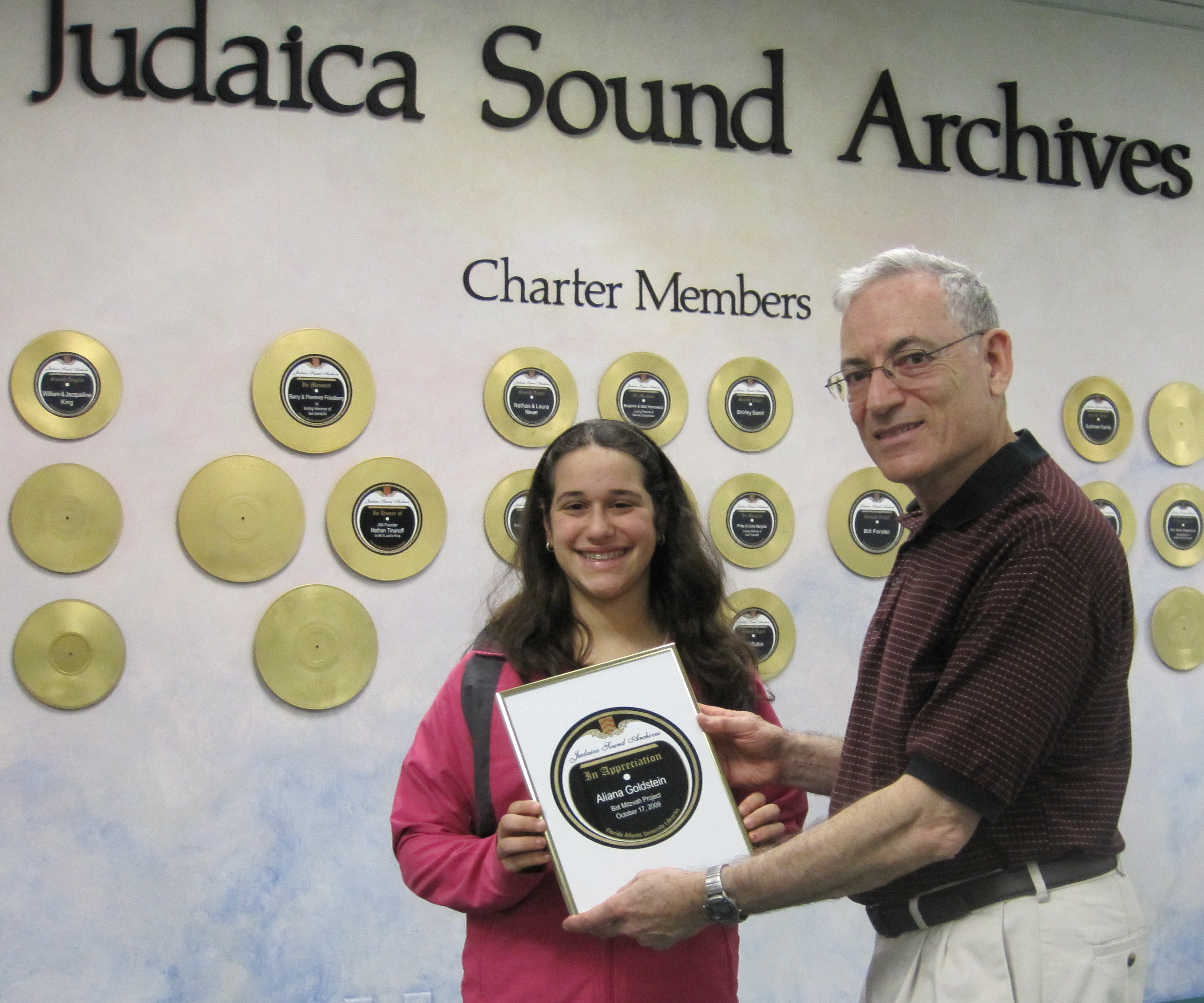 Ariana Goldstein recieves recognition plaque from Nathan Tinanoff on the completion of her Mitzvah Project